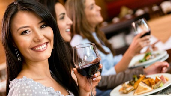 women drinking wine at dinner