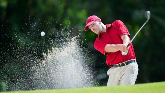 man golfing out of sandpit