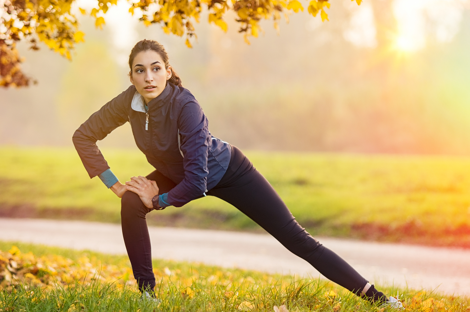 Young woman stretching and warming up at park during sunset. Att
